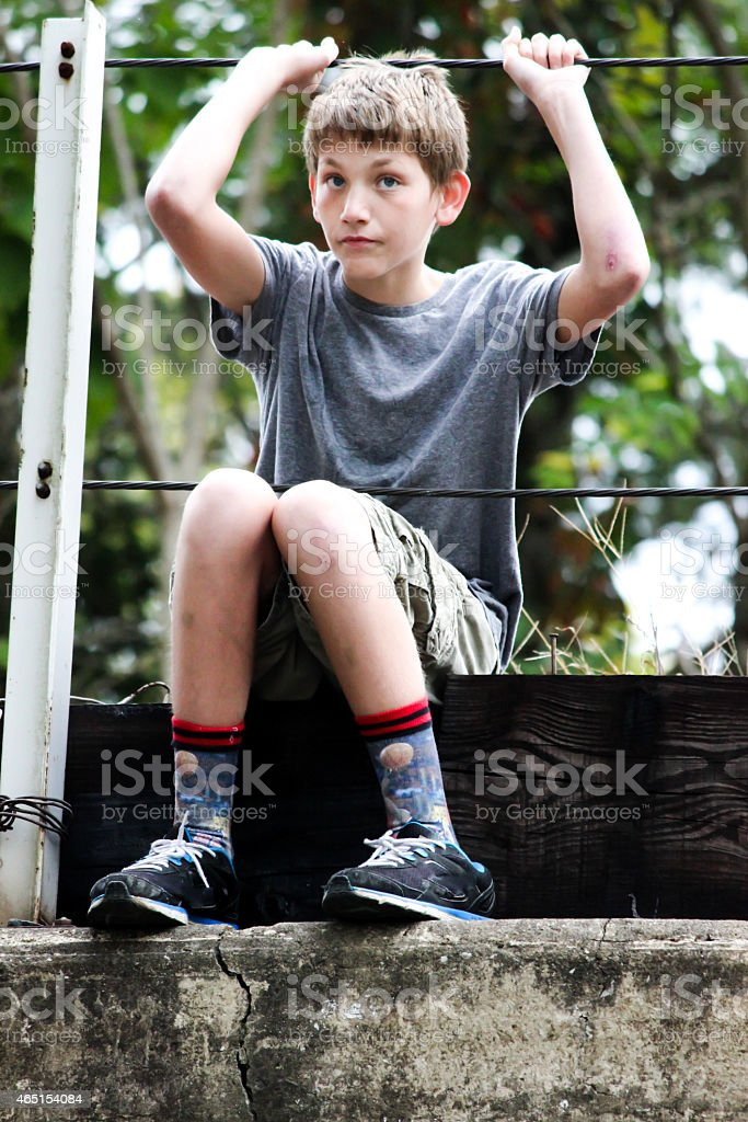Young Boy Sits On Top of Railroad Bridge stock photo