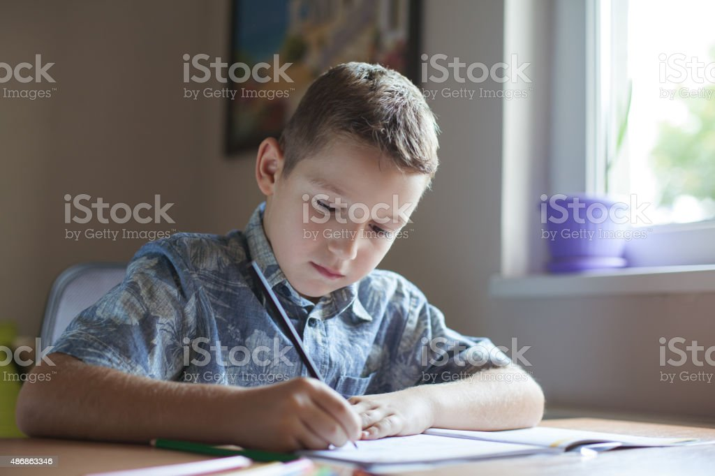 Young boy sitting at the table doing his school homework. stock photo