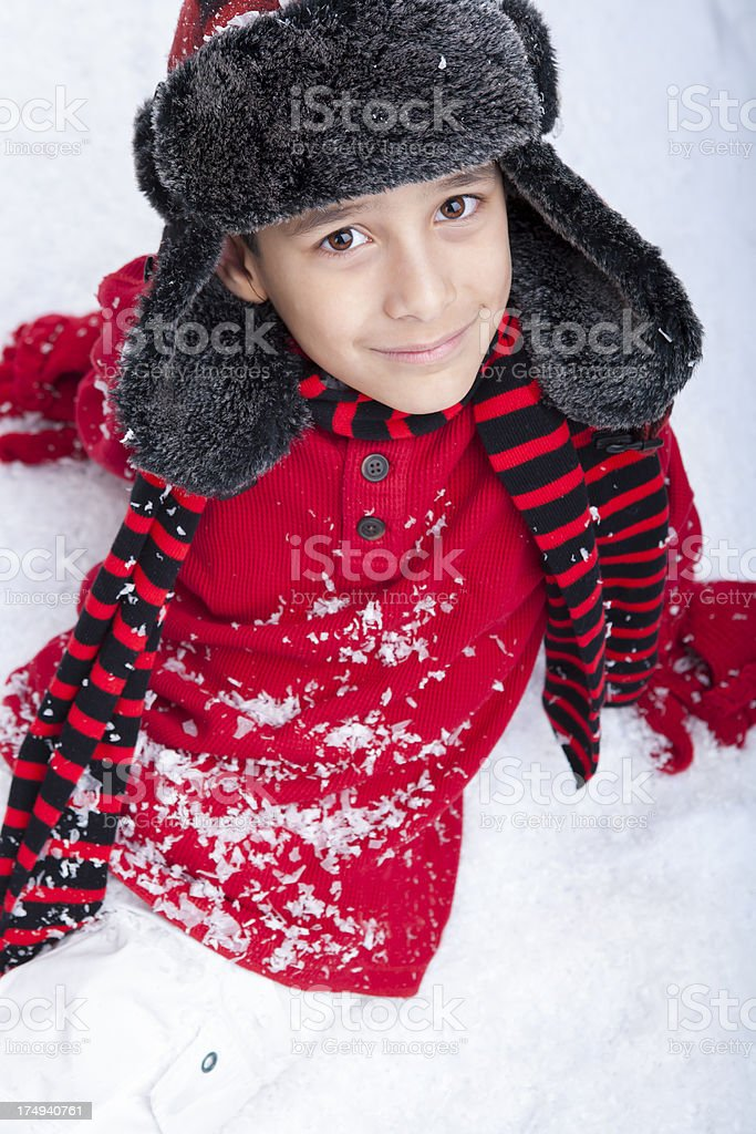 Young boy sitting back in the snow royalty-free stock photo