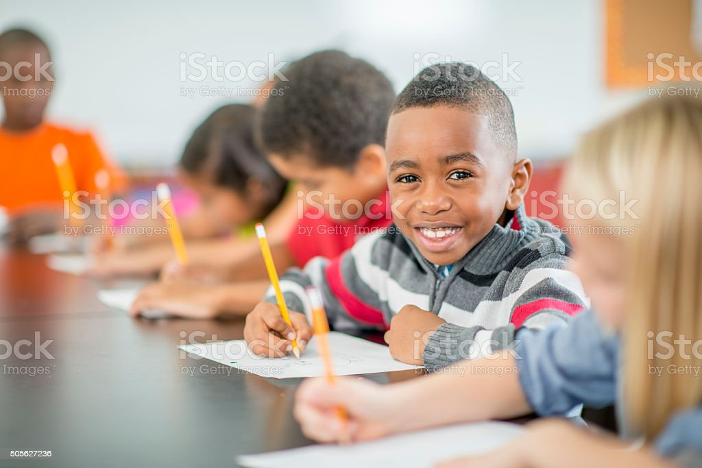 Young Boy Sitting Happily in Class stock photo