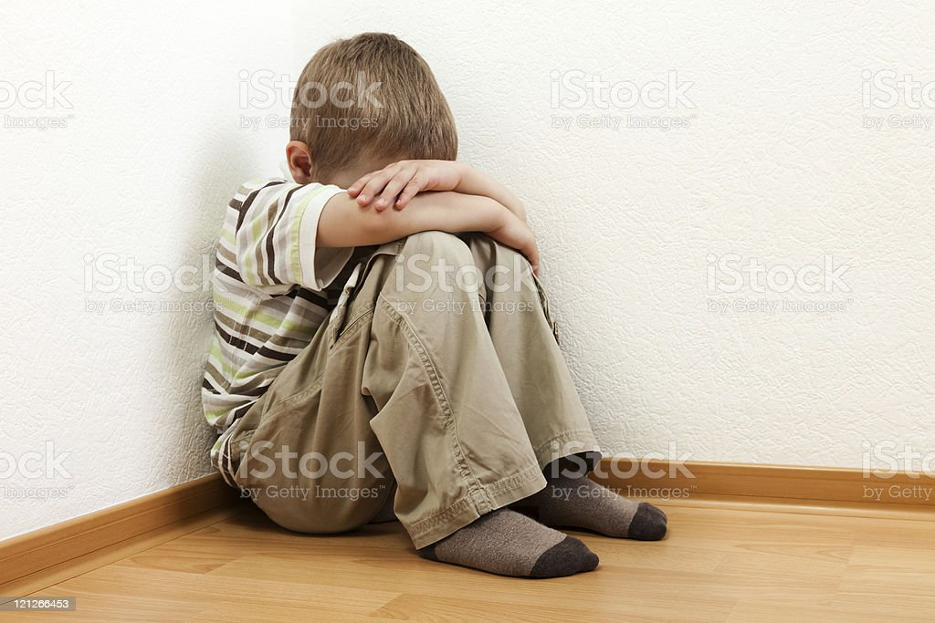 Young boy sitting in corner with head bowed into chest stock photo
