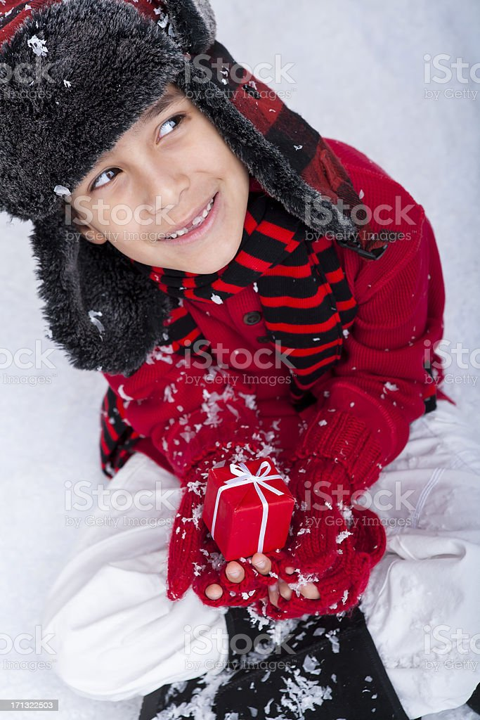 Young boy sitting in the snow with a present royalty-free stock photo