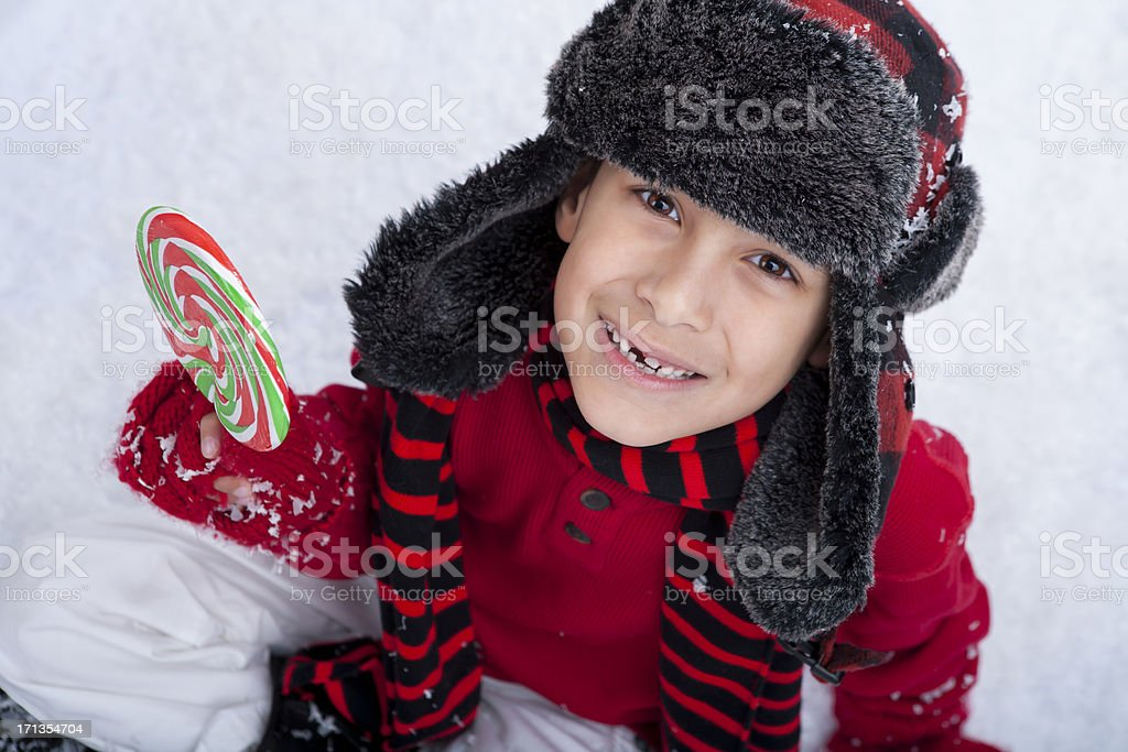 Young boy sitting in the snow with candy royalty-free stock photo