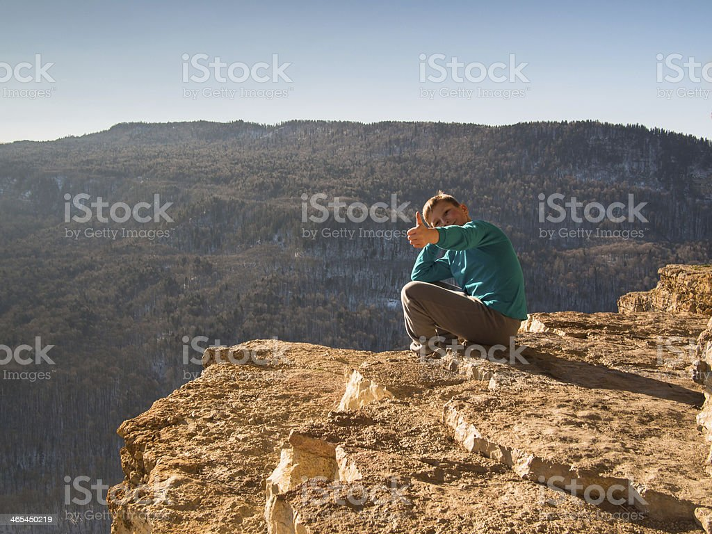 Young boy sitting on a rock and smiling stock photo