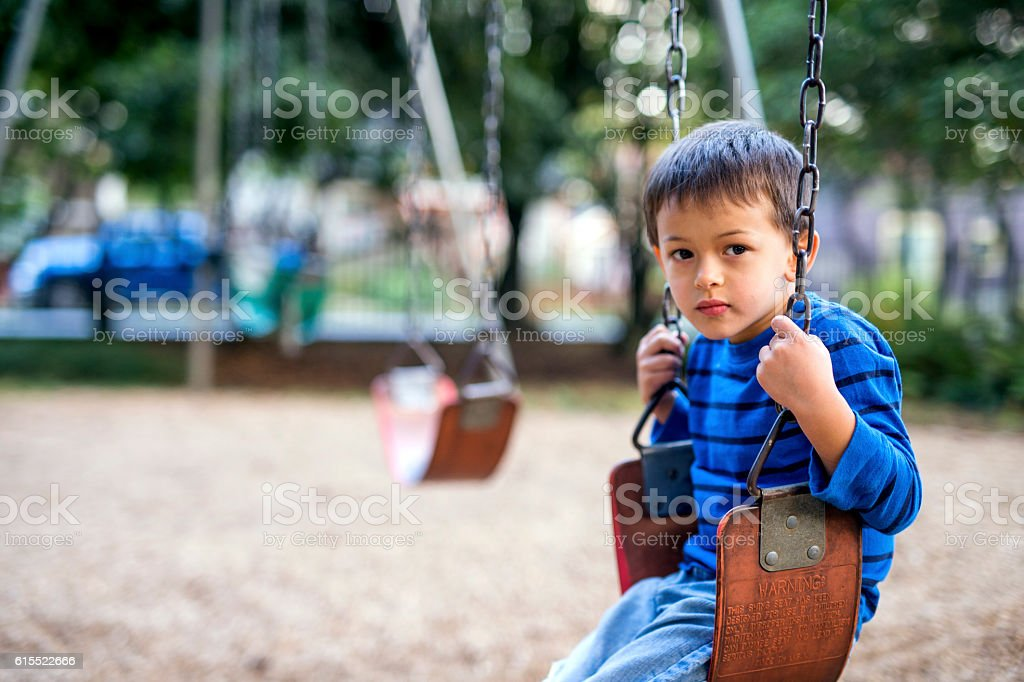Young boy sitting on a swing looking sad stock photo