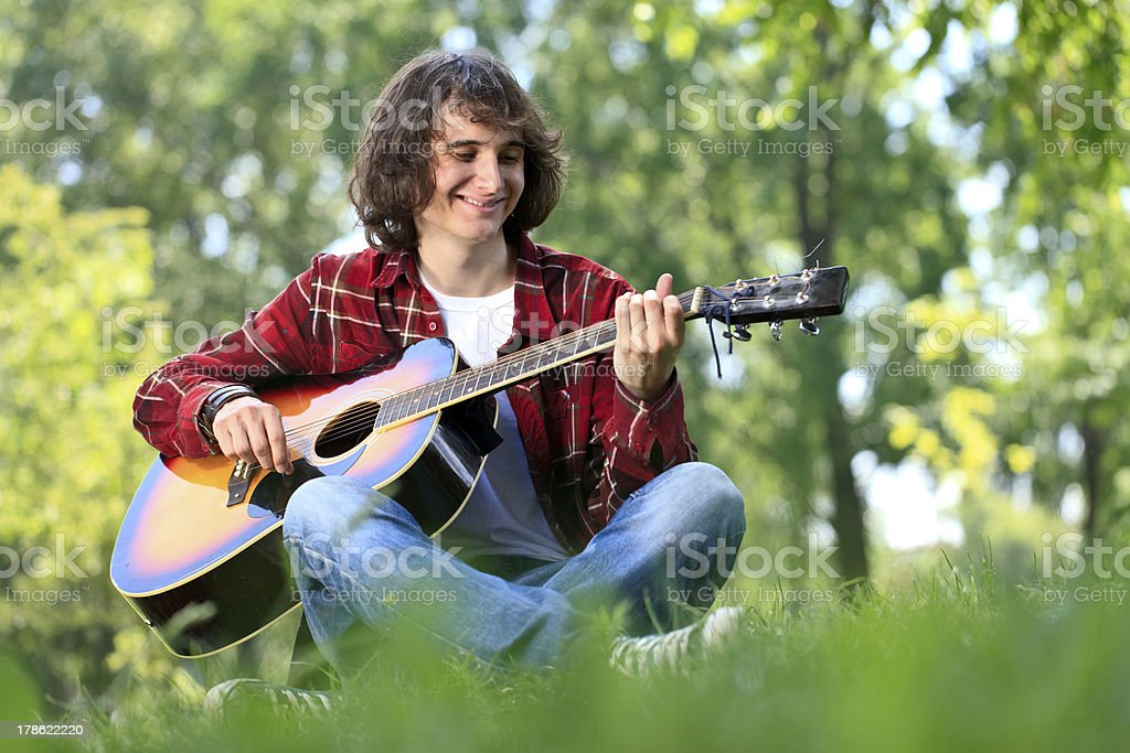 young boy sitting on grass with guitar royalty-free stock photo
