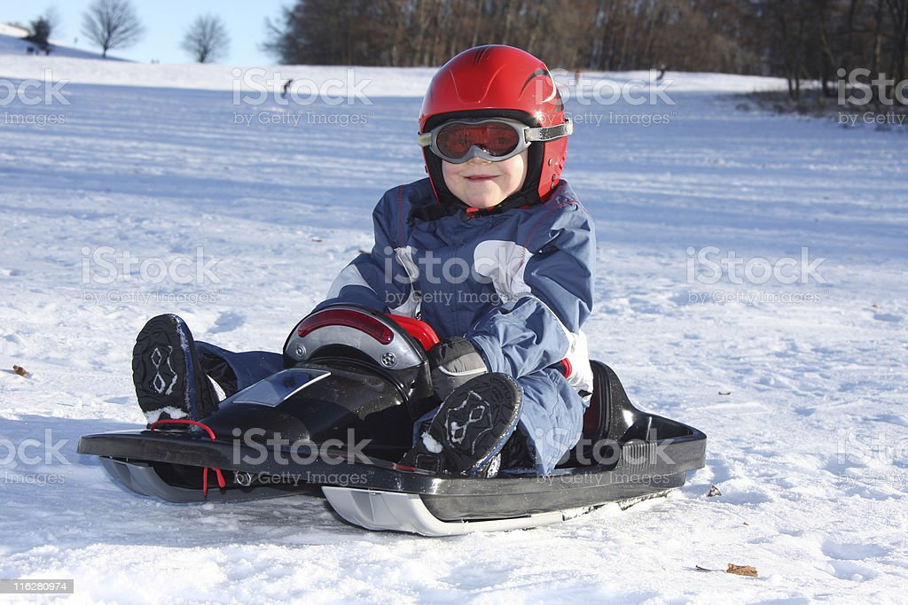 young boy sitting on his sledge royalty-free stock photo