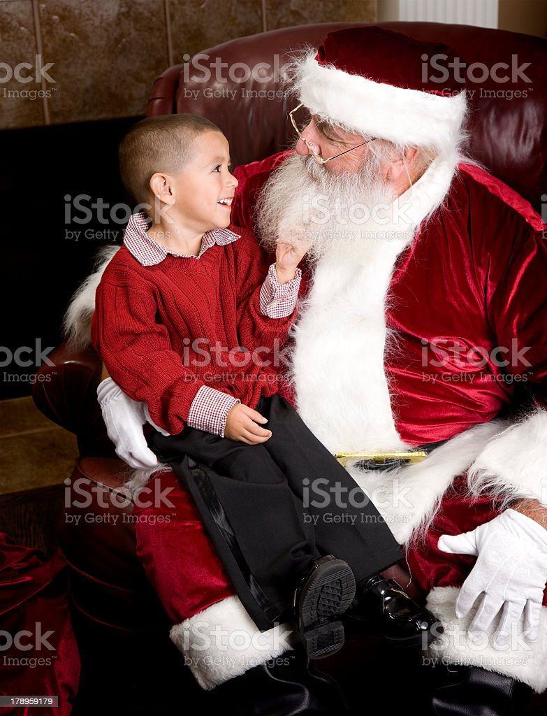 Young boy sitting on Santa Claus' lap and touching his beard stock photo