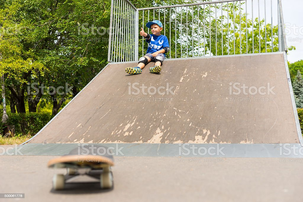 Young Boy Sitting on Top of Ramp in Skate Park stock photo