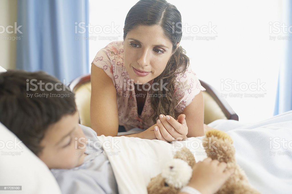 Young boy sleeping in hospital bed with teddy bear and woman looking over him royalty-free stock photo