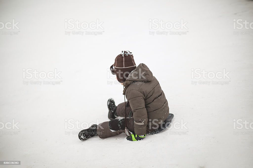 Young boy sliding down the hill on snow stock photo