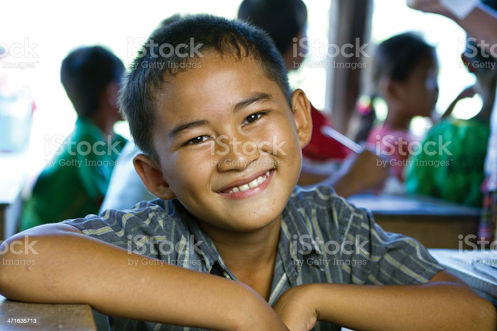 Young boy smiling at his desk at school stock photo