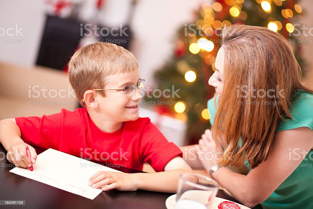 Young Boy Smiling at Mom While Writing Letter to Santa royalty-free stock photo