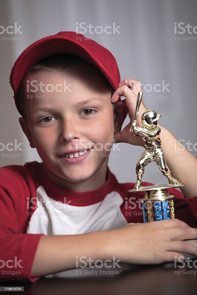 Young boy smiling, holding baseball trophy stock photo