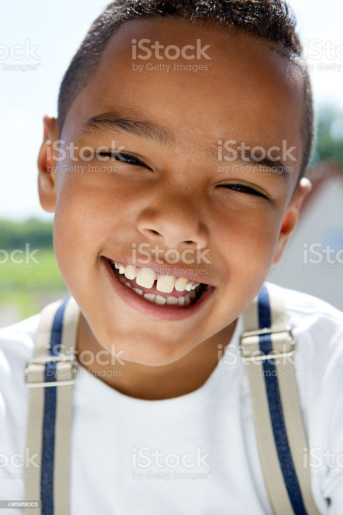 Young boy smiling with suspenders stock photo