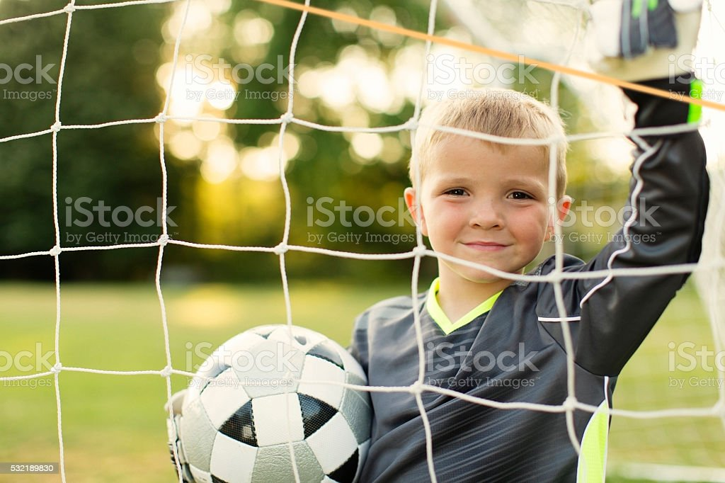 Young Boy Soccer Goalie Stands holding Ball stock photo