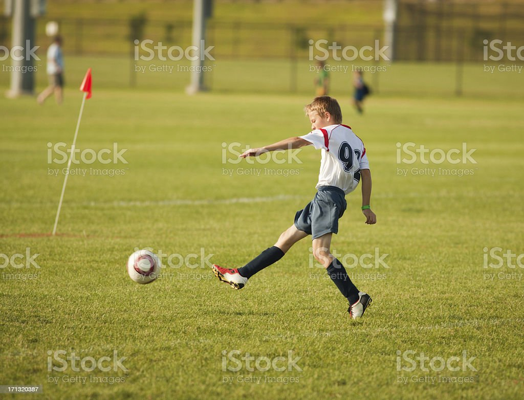 Young Boy Soccer Player Kicking the Ball into Goal stock photo