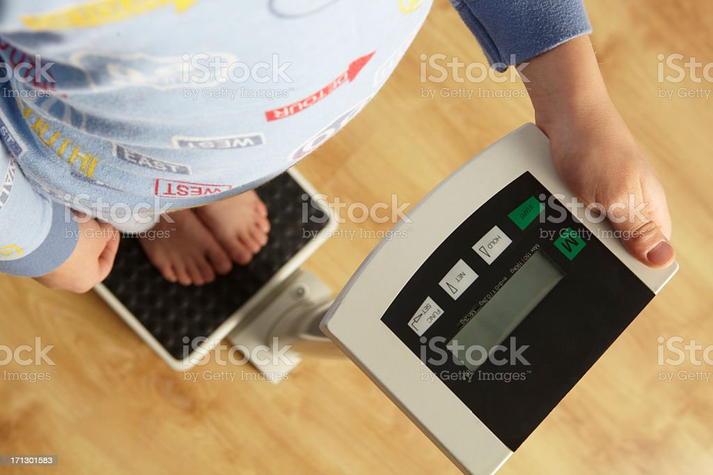 Young boy standing on digital scales cropped stock photo