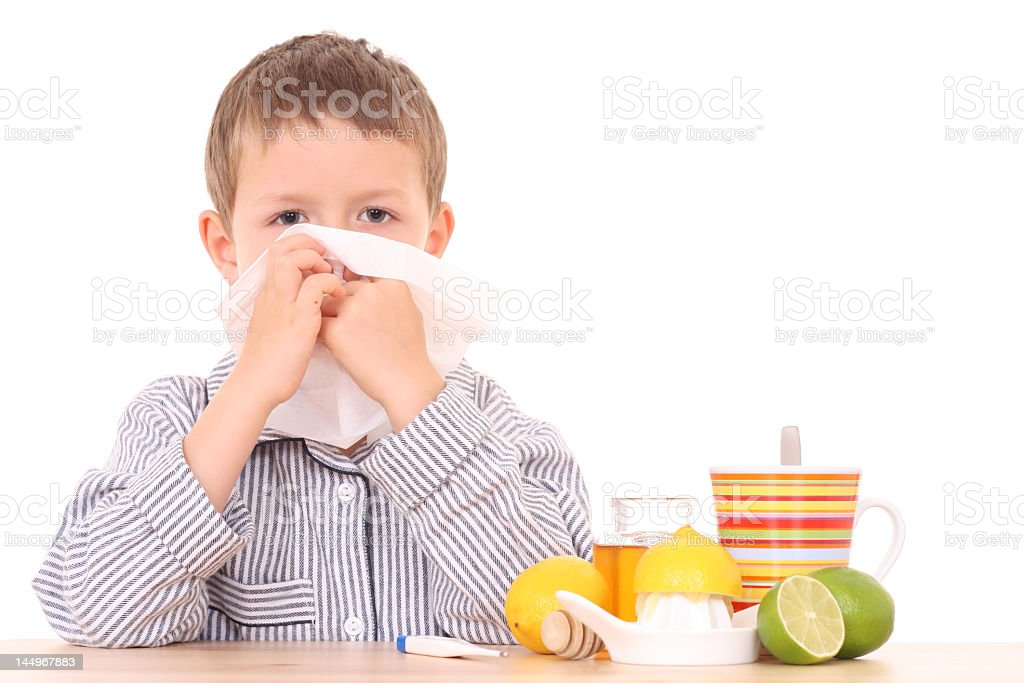 Young boy surrounded by citrus and tea blowing his nose royalty-free stock photo