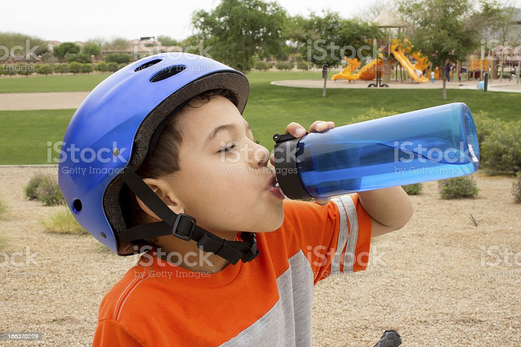 Young boy taking a break from riding his bike to rehydrate stock photo