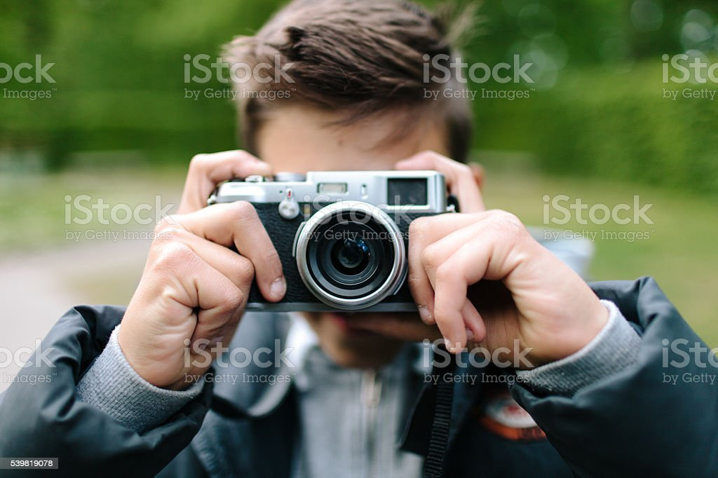 Young boy taking a picture stock photo