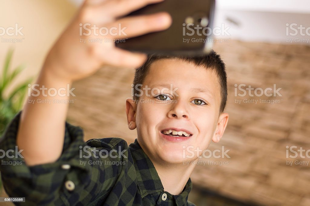 Young Boy Taking Selfie and Smiling stock photo