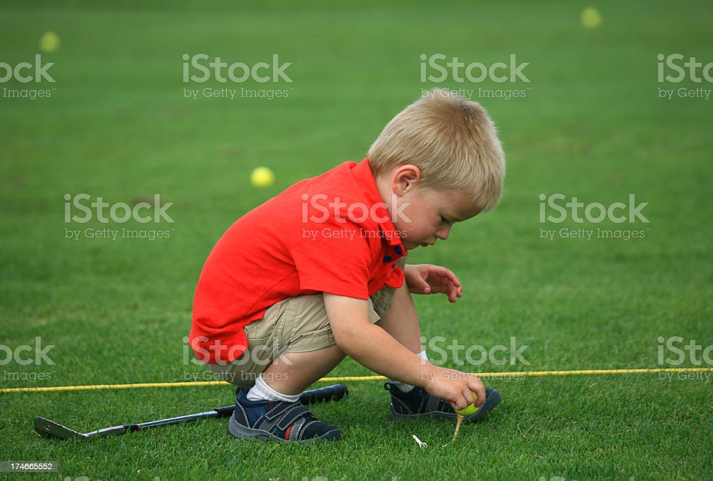 Young Boy Teeing Up a Golf Ball royalty-free stock photo