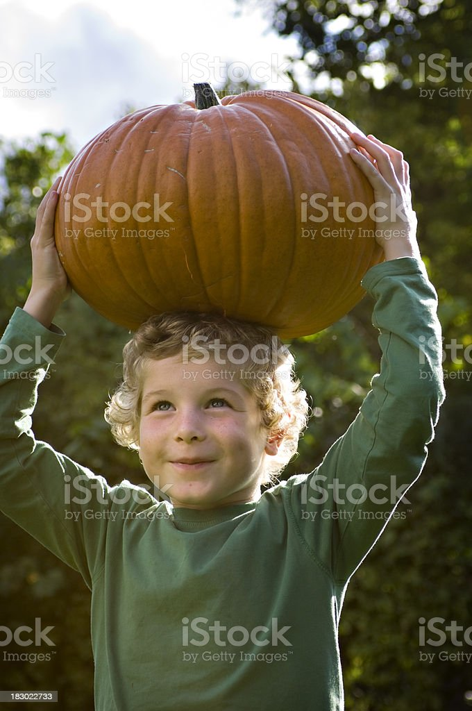 Young Boy Trying To Balance A Pumpkin On HIs Head stock photo