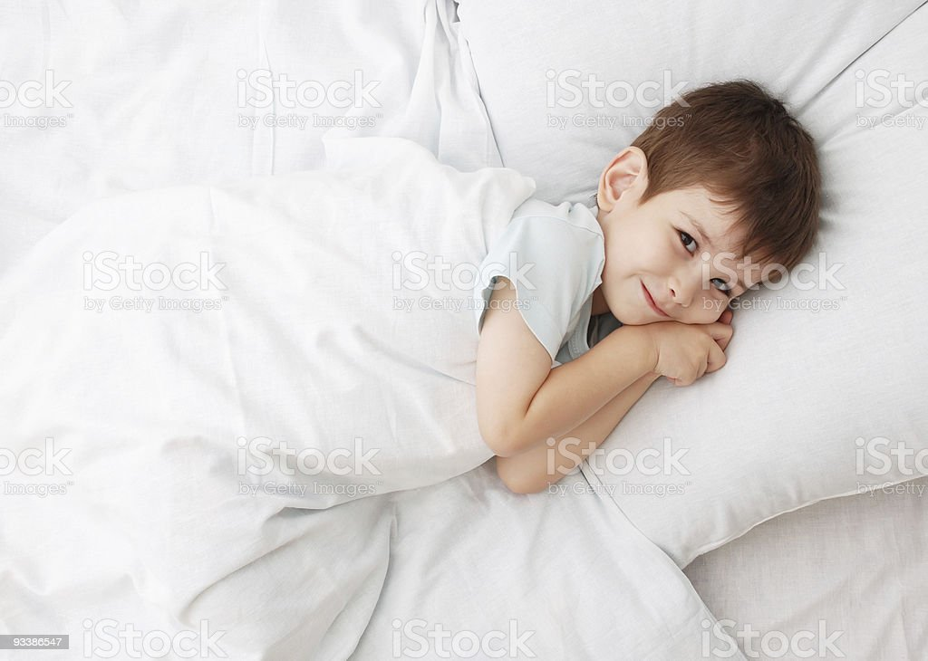 Young boy tucked in bed under a white blanket royalty-free stock photo