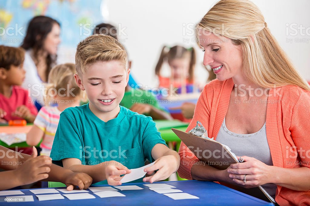 Young boy using flashcards to study with teacher stock photo