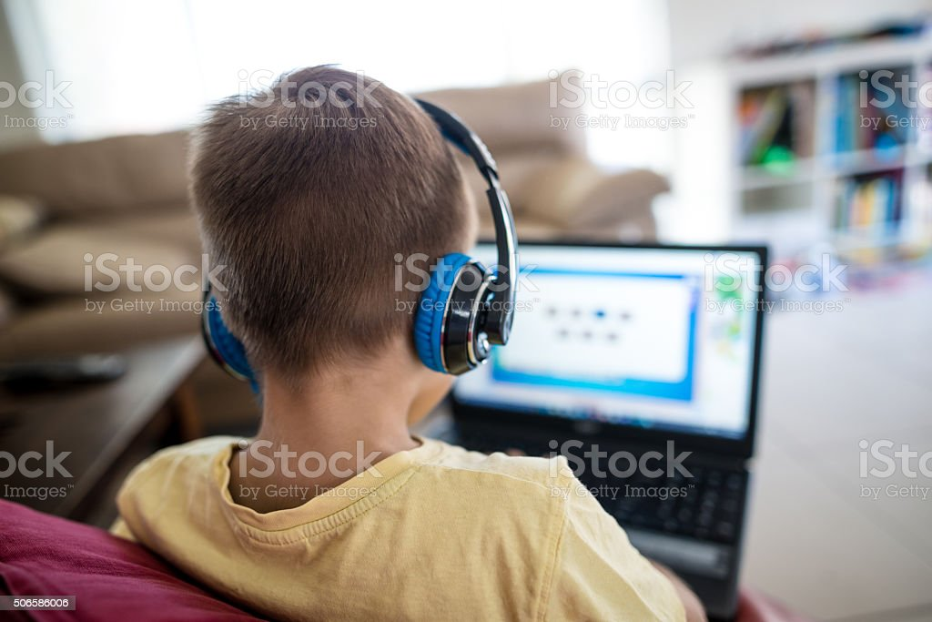 Young boy using laptop and listening with headphones stock photo