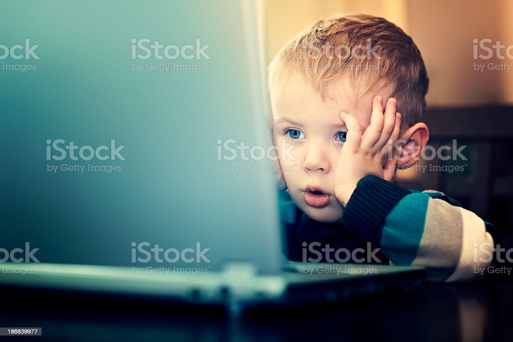Young boy using laptop computer stock photo