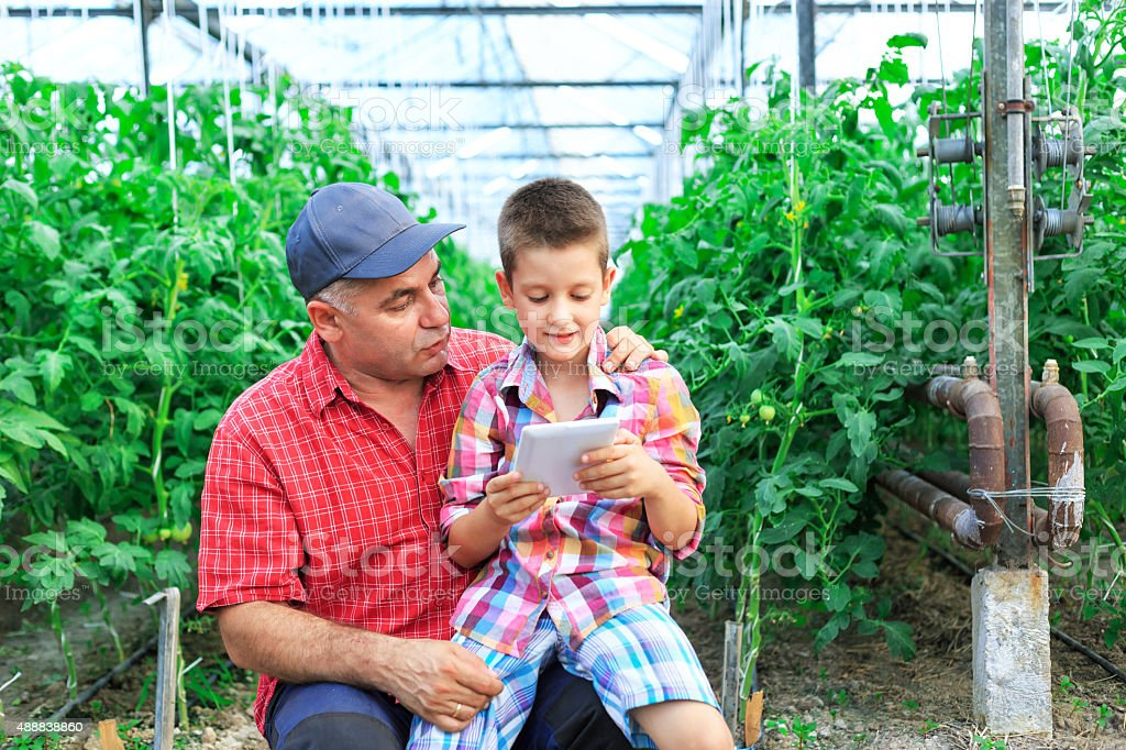 Young boy using  tablet with his father stock photo