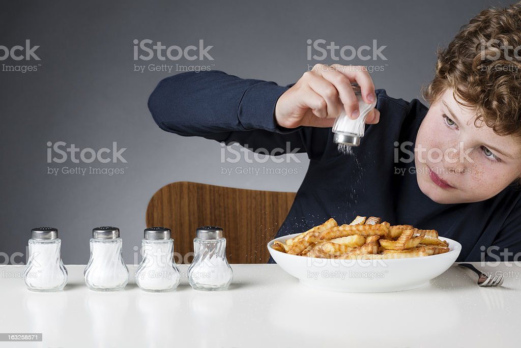 Young Boy Using Too Much Salt stock photo