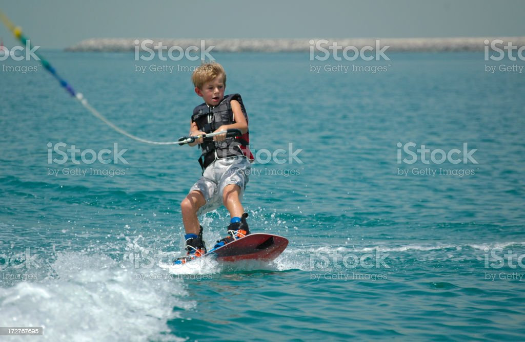 Young boy wake boarding on ocean stock photo