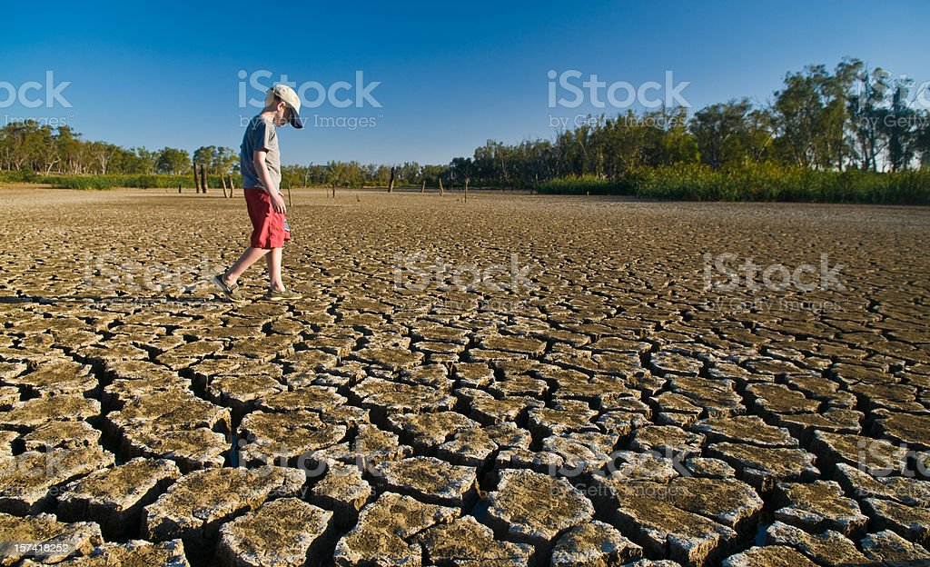 Young boy walking on a dry lake bed looking down stock photo