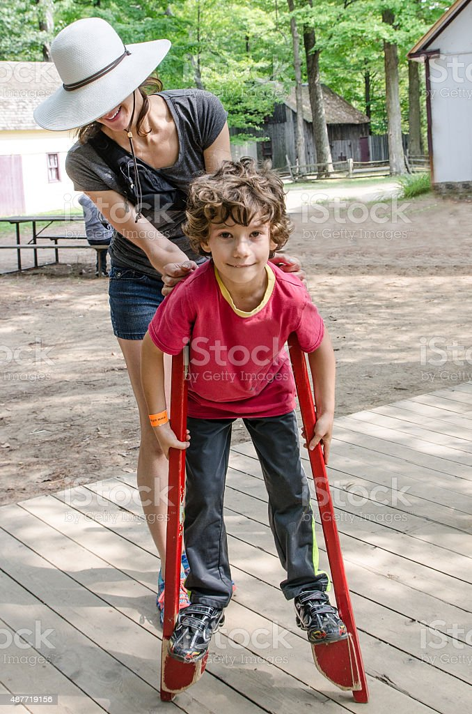 Young boy walking with stilts stock photo