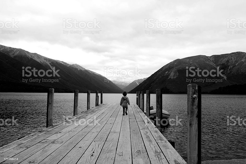Young boy walks down jetty on a moody day stock photo