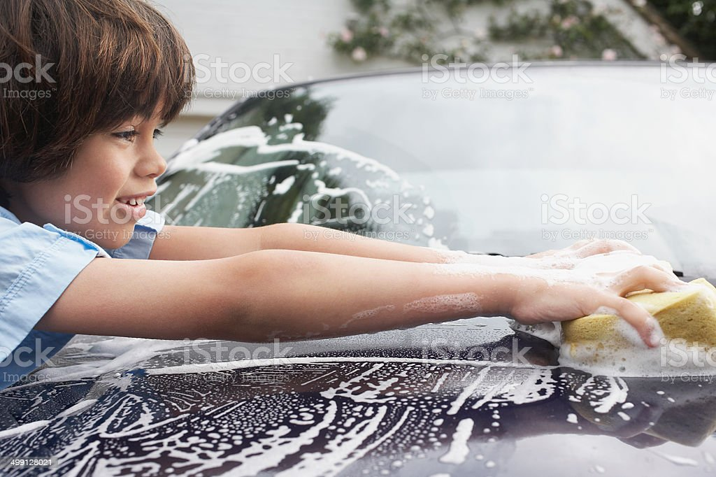 Young Boy Washing Car With Sponge stock photo