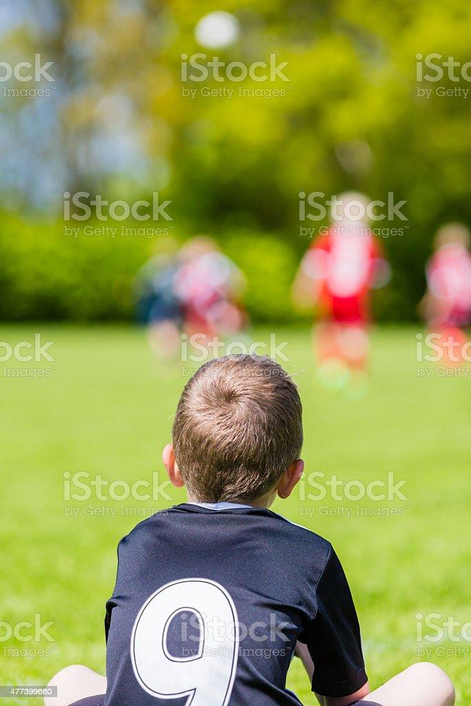 Young boy watching a kids soccer match stock photo