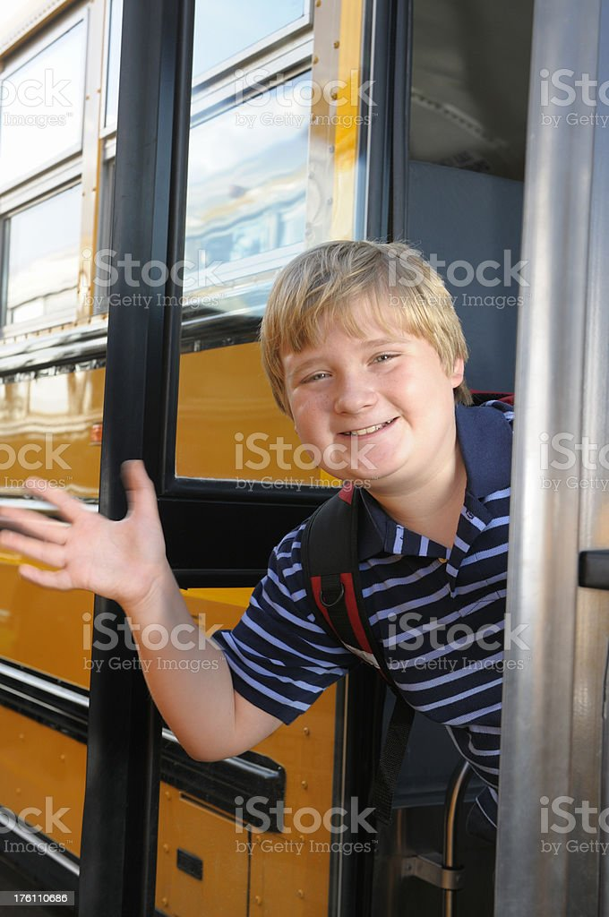 Young boy waving from the school bus royalty-free stock photo
