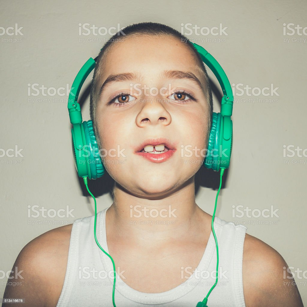 Young boy wearing a green headphones listening to the music stock photo