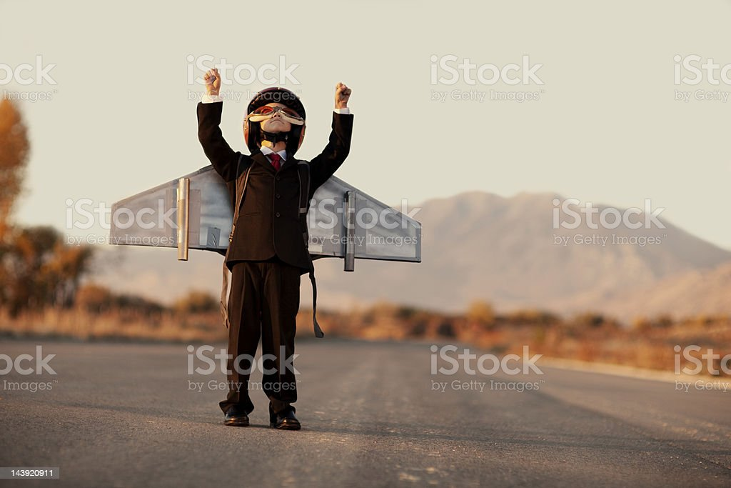 Young Boy Wearing Business Suit and Jet Pack on Blacktop stock photo