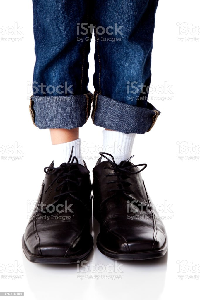 Young Boy Wearing Dads Shoes stock photo