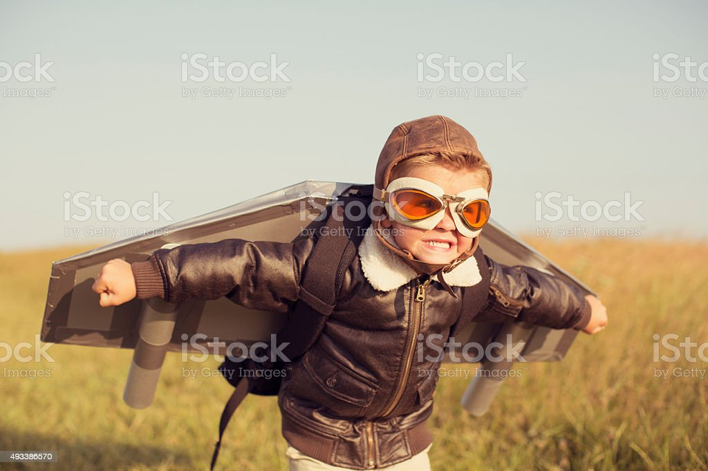 A young boy wearing a bomber jacket and goggles is ready to fly his...