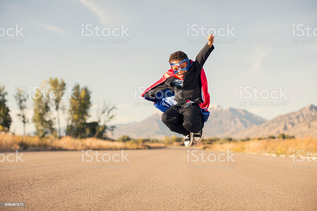 Young Boy Wearing Superhero Costume and Business Suit is Jumping stock photo