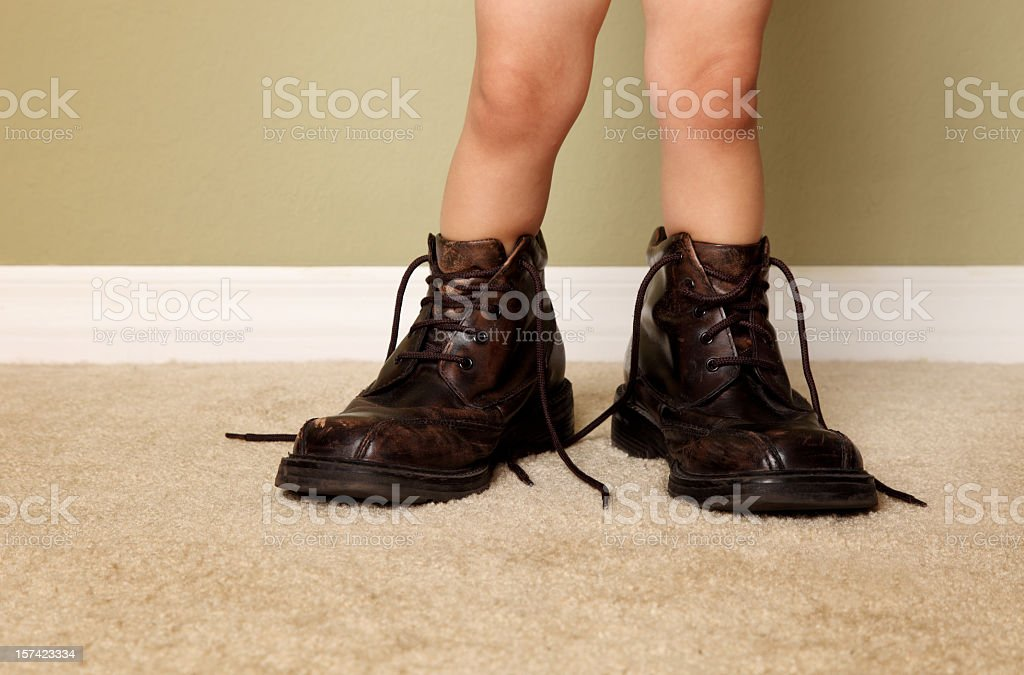 A young boy who decided to try on his father's shoes  stock photo