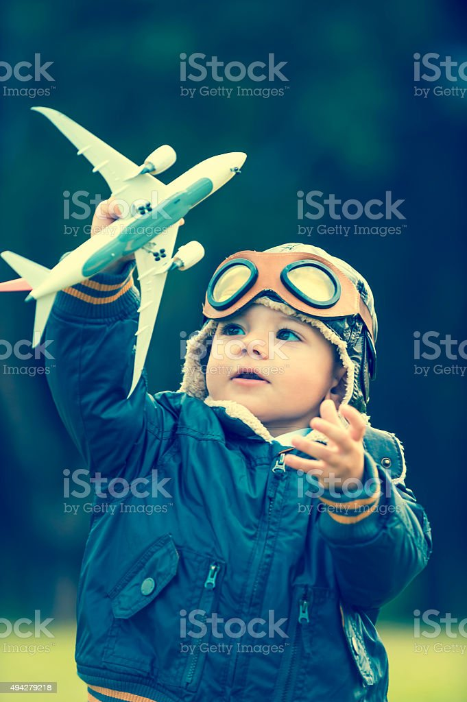 Young boy with a aviator outfit and airplane. stock photo