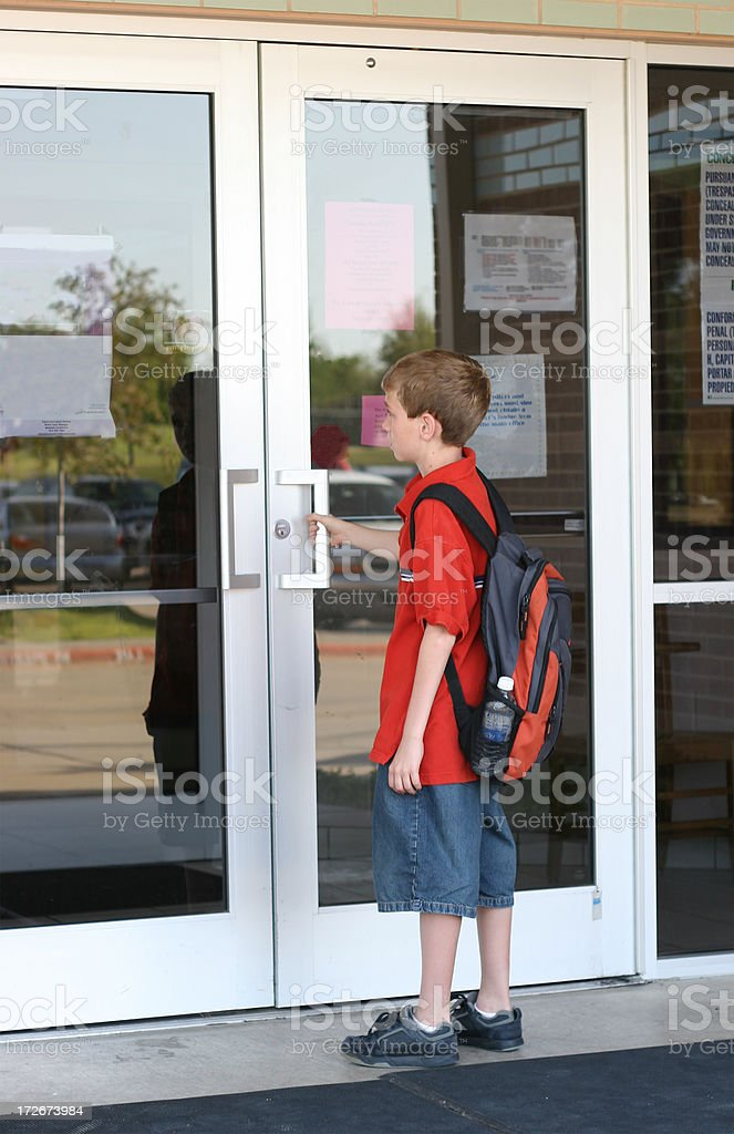A young boy with a backpack opening the doors to school royalty-free stock photo