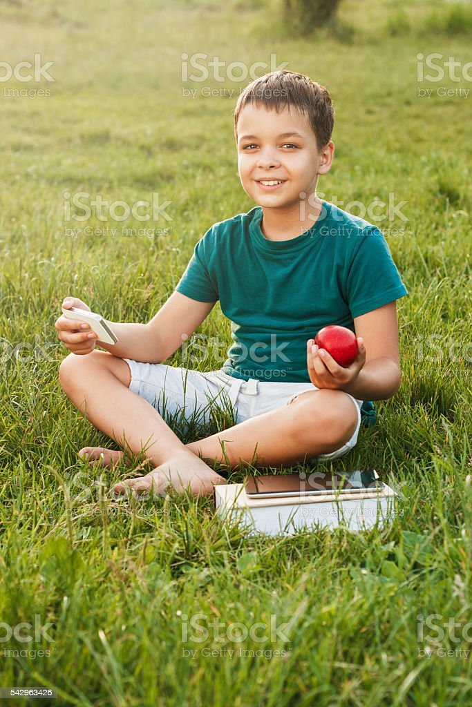 Young boy with a phone on the grass stock photo